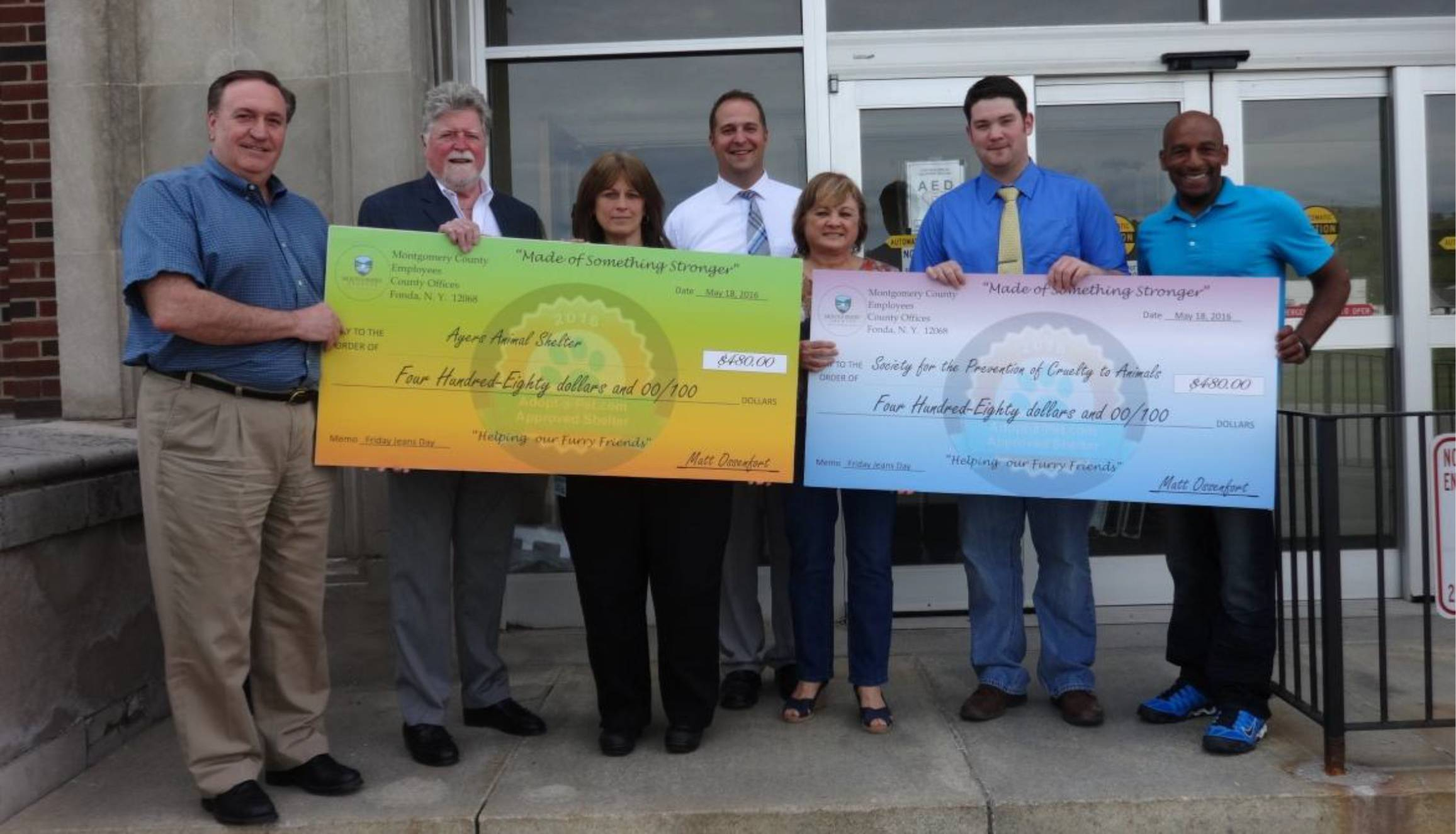 County officials present the Ayers Animal Shelter and the Montgomery County SPCA with checks for money raised by county employees during 'Jeans Days'