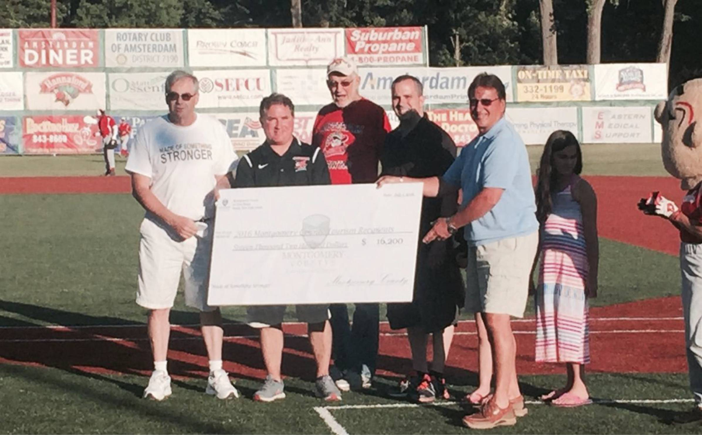 Montgomery Count Legislators gift check for the 2016 Local Tourism Grant Awards to organizations at the Amsterdam Mohawks game on