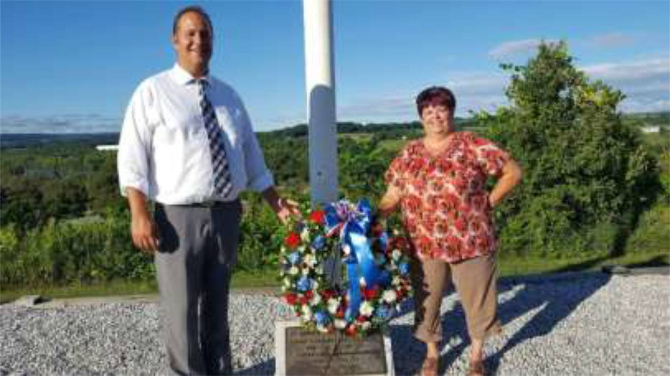 Montgomery County Executive Matthew L. Ossenfort and Town of Minden Supervisor Cheryl Reese pose at flagpole monument.