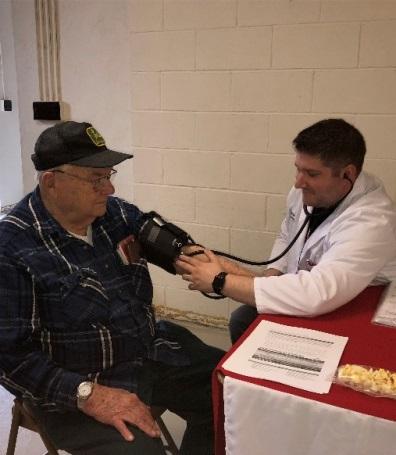 Pharmacist Joshua Baker checks Allan Taylor's blood pressure Thursday during the Public Health Department's Senior Meet and Greet.