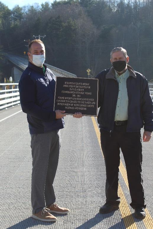 Montgomery County Executive Matthew L. Ossenfort stands with former Department of Public Works Commissioner Paul Clayburn after dedicating the Burtonsville Road Spur Bridge to him during a ribbon cutting ceremony for the structure Thursday.